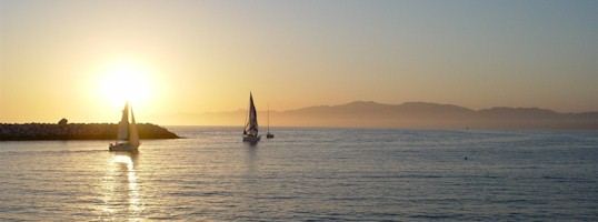 Near sunset, two sailboats round the north end of the detached breakwater at Marina del Rey, California